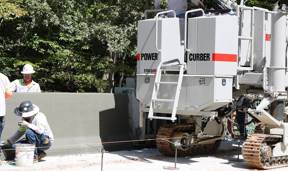Powers Curbers 5700-D Slipform Machine Paving A Highway Safety Barrier